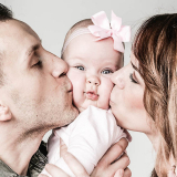 Baby krijg kus van Papa en Mama tijdens de fotoshoot
