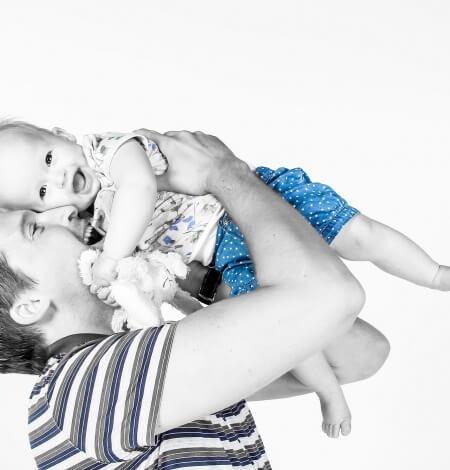 kindje hoog gehouden door vader met knuffel
